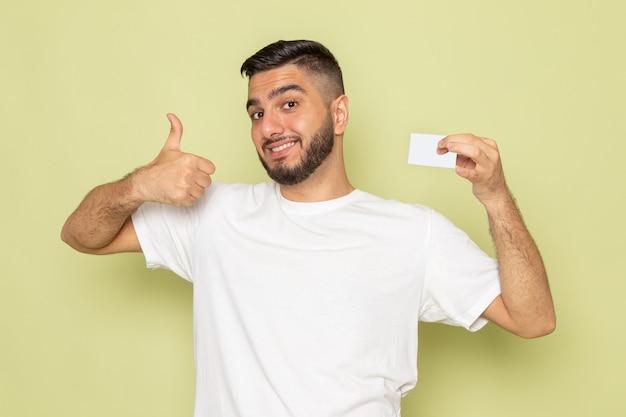 Un hombre joven de vista frontal en camiseta blanca sonriendo y sosteniendo una tarjeta blanca