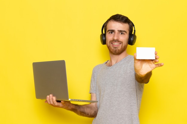 Un hombre joven de vista frontal en camiseta gris sosteniendo una tarjeta blanca y usando una computadora portátil con una sonrisa en la pared amarilla hombre expresión emoción modelo de color