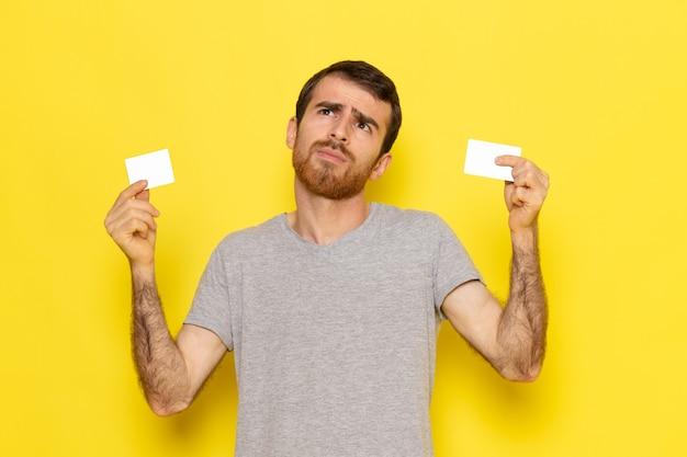 Un hombre joven de vista frontal en camiseta gris sosteniendo tarjetas blancas en la pared amarilla hombre expresión emoción modelo de color