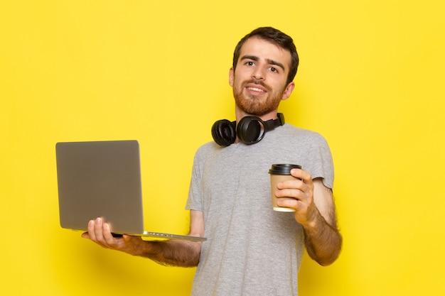 Un hombre joven de vista frontal en camiseta gris sosteniendo una taza de café y usando una computadora portátil con una sonrisa en la pared amarilla hombre expresión emoción modelo de color
