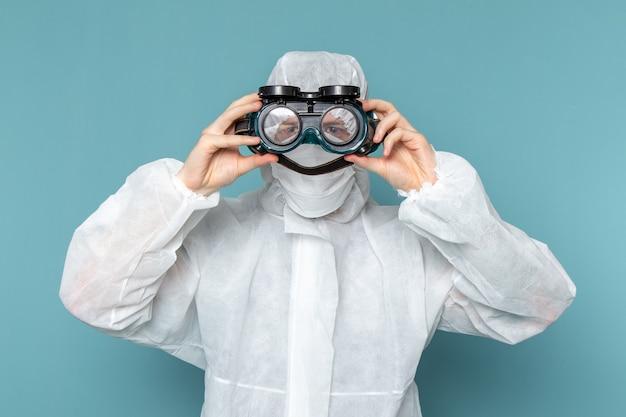 Un hombre joven de vista frontal en traje especial blanco con gafas de sol especiales en la pared azul traje de hombre peligro equipo especial color