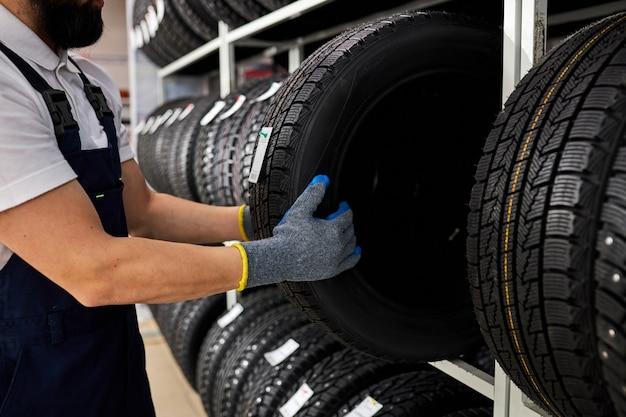 Hombre de jubilación tocando y eligiendo para comprar un neumático, midiendo la rueda del coche de goma, sacándola del estante con surtido
