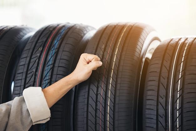 Hombre de jubilación tocando y eligiendo para comprar un neumático en un supermercado. medición de la rueda del coche de goma.
