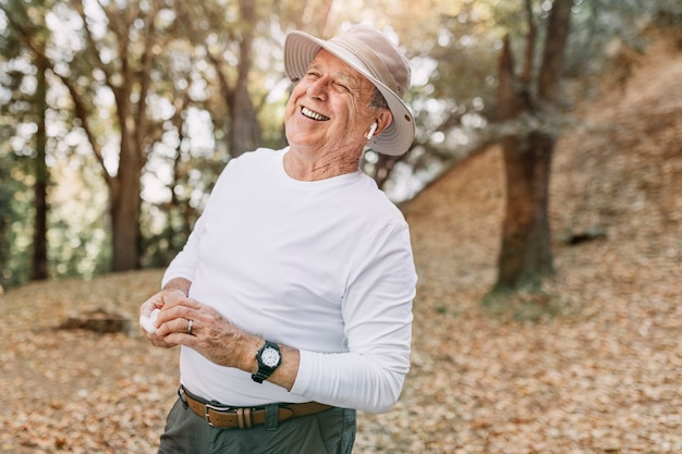 Hombre jubilado disfrutando de la música en medio del bosque