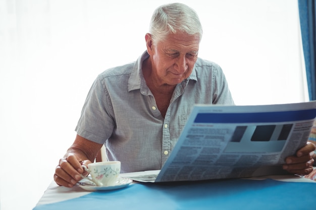 Hombre jubilado leyendo las noticias mientras sostiene una taza de té