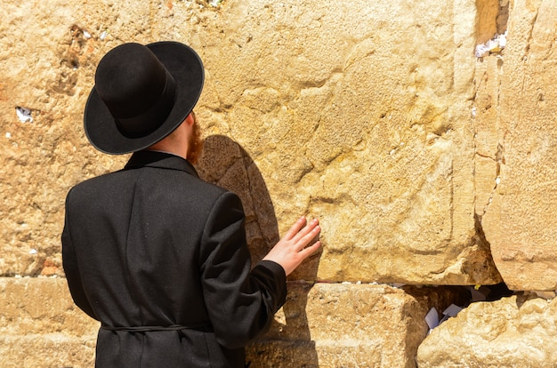 Hombre judío ortodoxo rezando en el muro occidental en jerusalén, israel