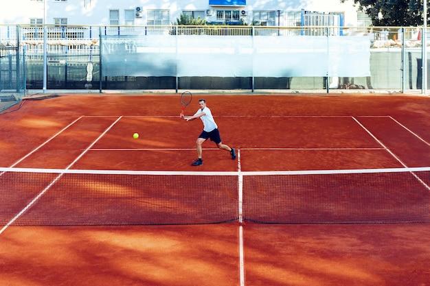 El hombre juega al tenis en el campo de tenis de arcilla vista desde lejos