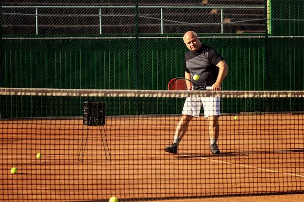El hombre juega al tenis en la cancha. estilo de vida activo y salud.