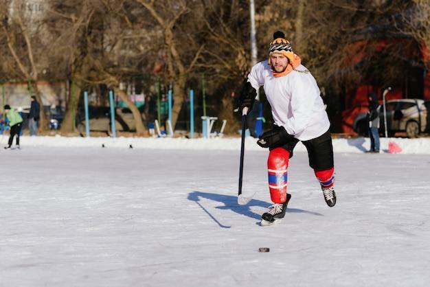 El hombre juega hockey en la pista