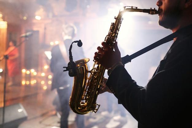 El hombre juega con un saxofón