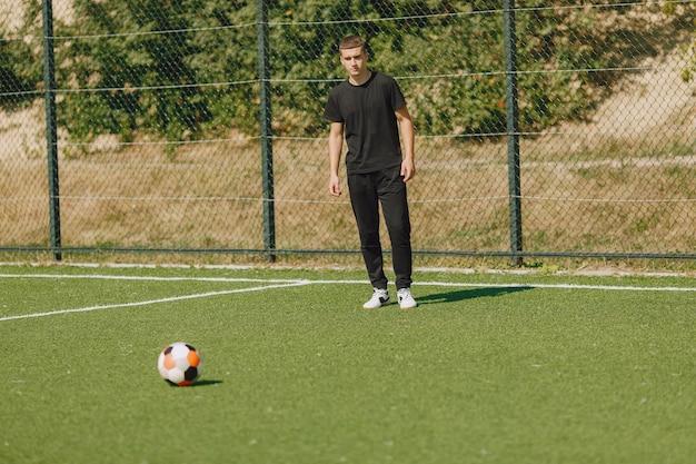 El hombre juega socerl en el parque. torneo de mini-fútbol. chico en trajes deportivos negros.