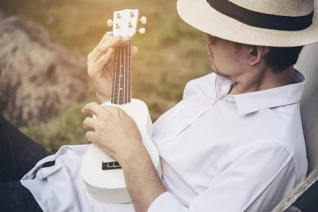 Hombre juega ukelele nuevo al rio.
