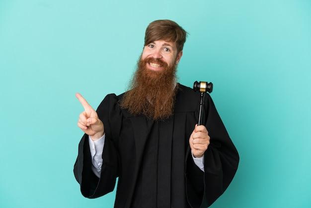 Hombre de juez caucásico pelirrojo aislado sobre fondo azul apuntando hacia el lado para presentar un producto