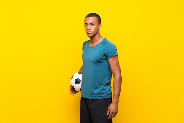 Hombre de jugador de fútbol americano afro sobre pared amarilla aislada