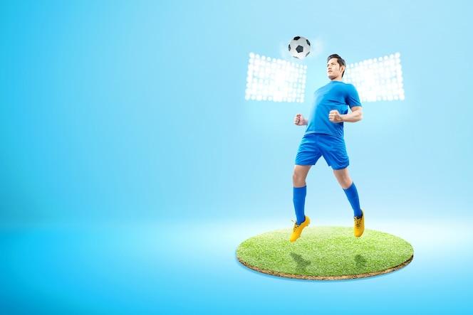 Hombre de jugador de fútbol asiático saltar y dirigir la pelota