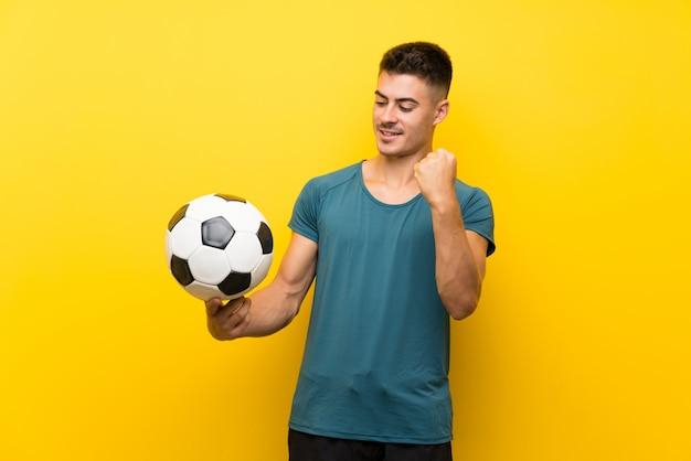 Hombre de jugador de fútbol joven guapo sobre fondo amarillo aislado celebrando una victoria