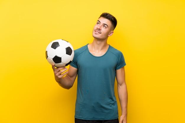Hombre de jugador de fútbol joven guapo sobre fondo amarillo aislado mirando hacia arriba mientras sonríe