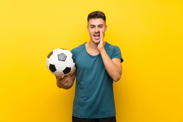Hombre de jugador de fútbol joven guapo sobre pared amarilla aislada gritando con la boca abierta