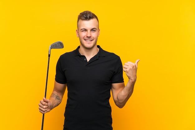 Hombre jugador de golf sobre fondo amarillo aislado apuntando hacia un lado para presentar un producto