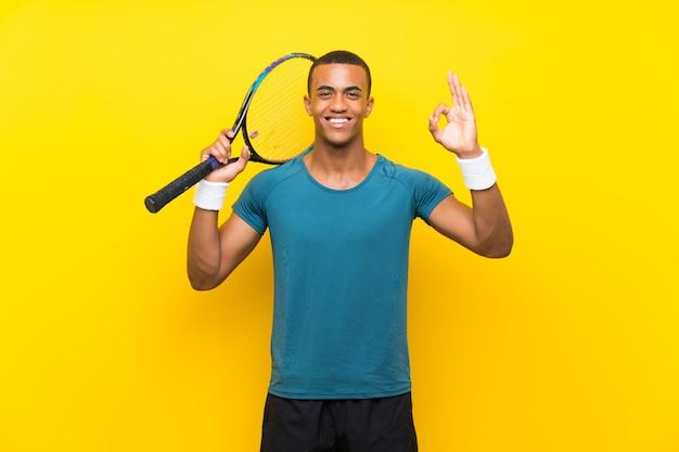Hombre de jugador de tenis afroamericano que muestra signo bien con los dedos