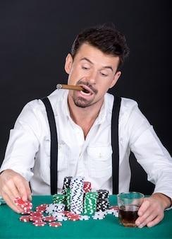 El hombre está jugando al póker con un cigarro y un vaso de whisky.