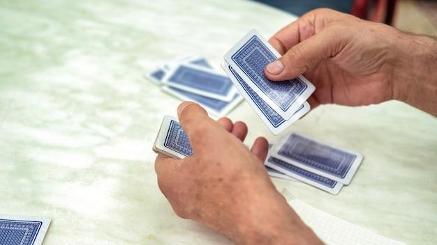 Un hombre jugando a las cartas con otras personas mezclando una baraja.