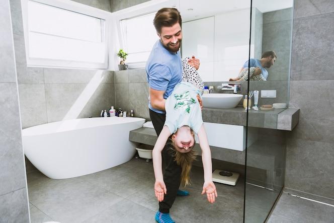Hombre jugando con hija en el baño