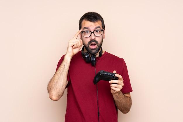 Hombre jugando con un controlador de videojuego sobre pared aislada con gafas y sorprendido
