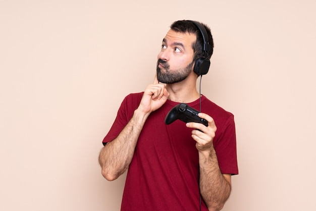 Hombre jugando con un controlador de videojuego sobre una pared aislada pensando en una idea mientras mira hacia arriba