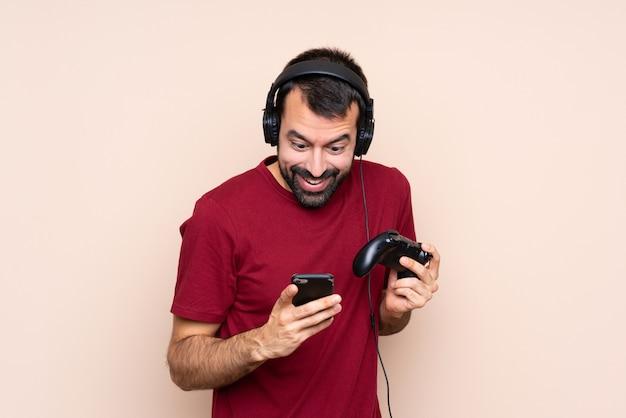 Hombre jugando con un controlador de videojuego sobre una pared aislada sorprendido y enviando un mensaje