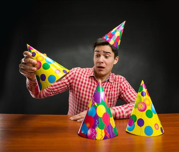Hombre jugando con gorros de cumpleaños