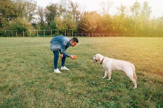 Hombre jugando con su perro labrador en pelota en el parque
