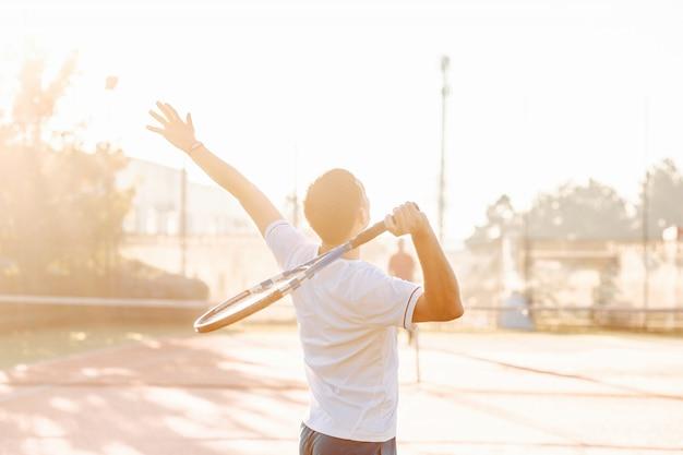 Hombre jugando tenis en la mañana a la luz del sol