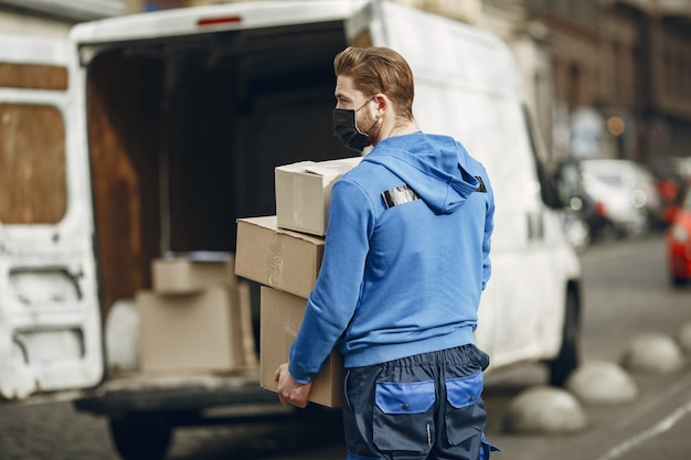 Hombre junto al camión. chico con uniforme de repartidor. hombre con una máscara médica. concepto de coronavirus.