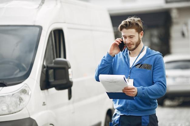 Hombre junto al camión. chico con uniforme de repartidor. hombre con portapapeles.