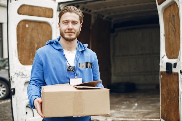 Hombre junto al camión. chico con uniforme de repartidor.