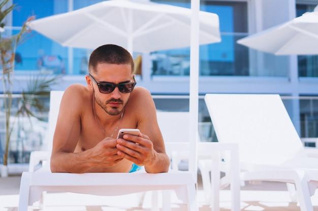 Hombre junto a la piscina con teléfono