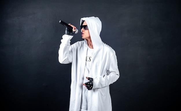 Un hombre de karaoke canta una canción en un micrófono, sobre un fondo oscuro y concreto. ¡un hombre divertido sostiene un micrófono en la mano a un cantante de karaoke que canta una canción! pivets contra fondo oscuro