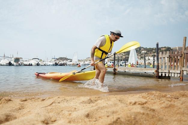 Hombre en kayak con gorra y chaqueta de seguridad amarilla