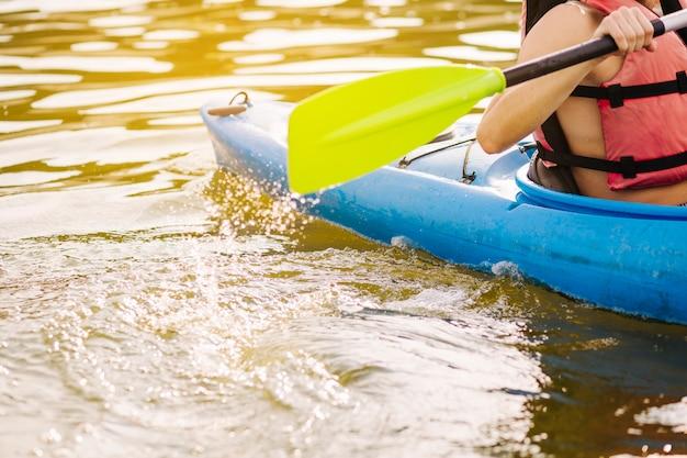 Hombre kayak con paleta en el lago