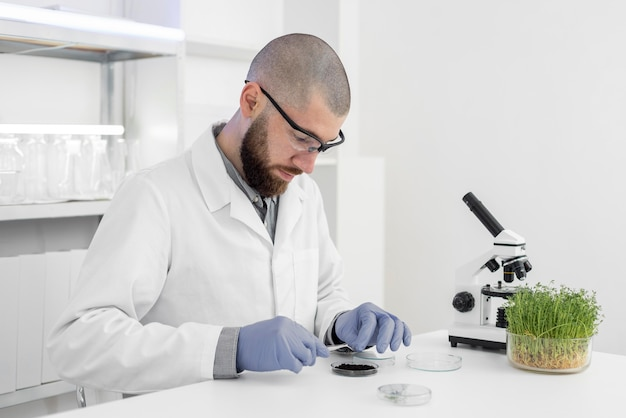 Hombre en laboratorio haciendo experimentos sobre brotes