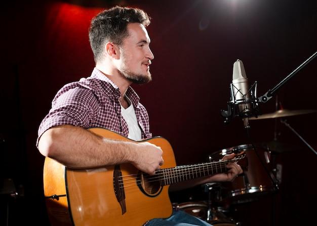 Hombre de lado tocando la guitarra acústica y mirando el micrófono
