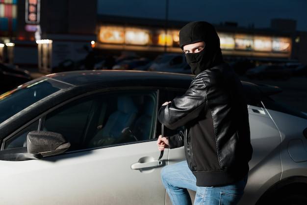 Hombre ladrón de coches puerta abierta con jemmy