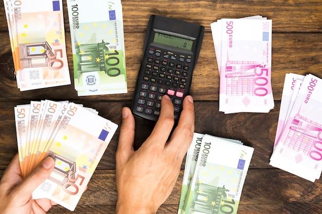Hombre laico plano contando dinero con calculadora
