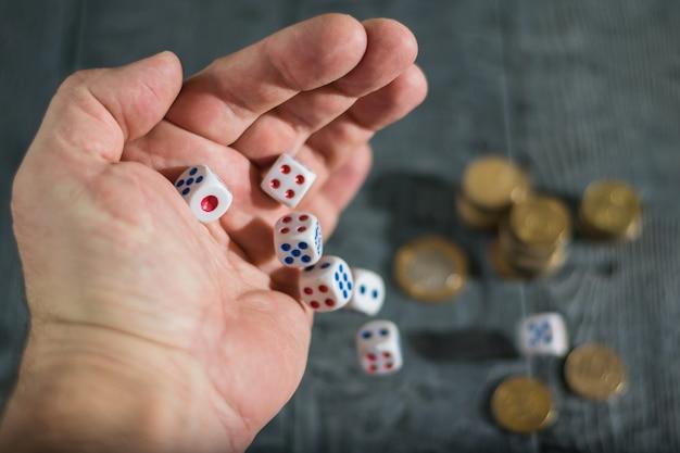 Un hombre lanza dados con marcas rojas y azules en la mesa de madera con monedas.