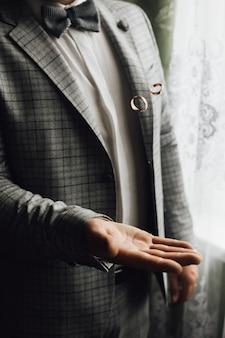 El hombre está lanzando dos anillos de boda