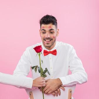 Hombre con lápiz labial marcas de besos en cara mirando rosa