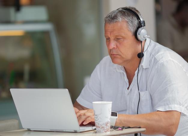 Hombre con laptop y auriculares sentado en la terraza de un café o restaurante.