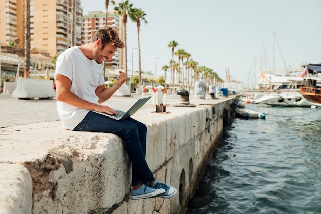 Hombre con laptop celebrando junto al río