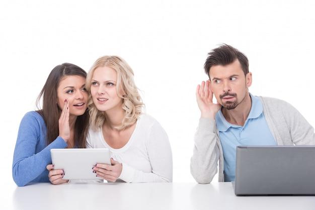 Hombre con laptop escucha chicas jóvenes.